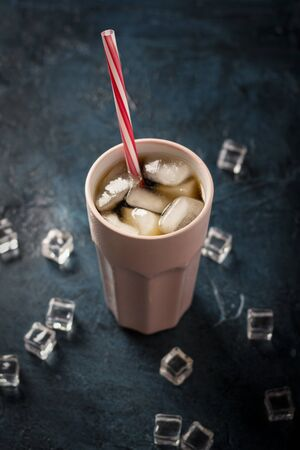 Iced coffee in a glass on a dark blue stone background with ice cubes. Concept cooling drink, thirst, summer, cola with ice, nightlife, club. Flat lay, top view. 写真素材 - 124719826