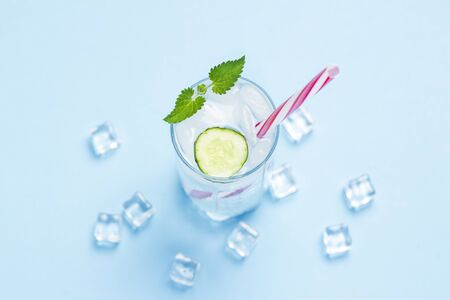Glass of cold and refreshing water with ice, mint and cucumber on a blue background. Ice Cube. Concept of hot summer, alcohol, cooling drink, thirst quenching, bar. Flat lay, top view.