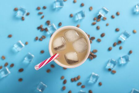 Refreshing coffee with milk and ice in a glass, ice cubes and coffee grains on a blue background. Concept summer, ice, refreshing cocktail, thirst. Flat lay, top view.