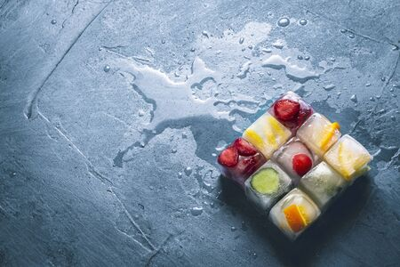 Ice cubes with fruit on a stone blue background. The shape of the square. Mint, strawberry, cherry, lemon, orange. Flatlay, top view.