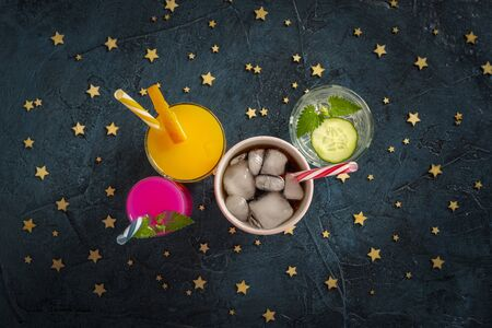 Four kinds of refreshing drinks with ice on a dark blue background and ice cubes. Concept night club, night life, party, thirst. Orange, mint and cucumber, strawberry, cola. Flat lay, top view.