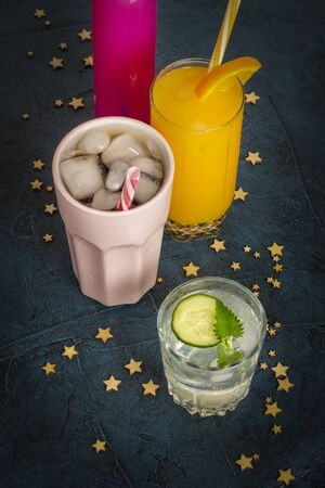Four kinds of refreshing drinks with ice on a dark blue background and stars. Concept night club, night life, party, thirst. Orange, mint and cucumber, strawberry, cola. Flat lay, top view.