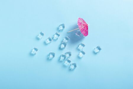Ice cubes and a decorative umbrella for a cocktail on a blue background. Flat lay, top view.