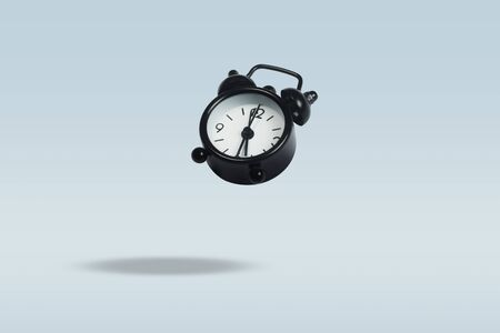 Flying Black alarm clock on a blue background. Levitation. Concept time management. Stock Photo