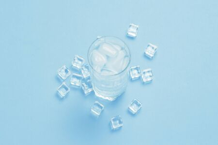 Glass of refreshing cold water with ice and ice cubes on a blue background. Concept of thirst, heat, refreshment in the summer. Flat lay, top view. Stock Photo