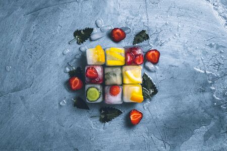 Ice cubes with fruit and broken ice on a stone blue background with mint leaves and fresh fruit. Cube shape. Mint, strawberry, cherry, lemon, orange. Flat lay, top view. Stock Photo