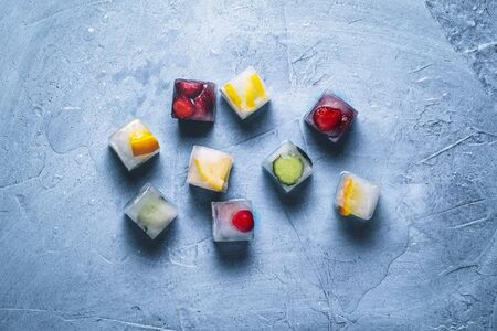 Ice cubes with fruit on a stone blue background. Mint, strawberry, cherry, lemon, orange. Flatlay, top view.