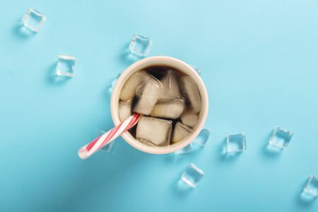 Refreshing iced coffee in a glass and ice cubes on a blue background. Concept summer, cola with ice, refreshing cocktail, thirst. Flat lay, top view.
