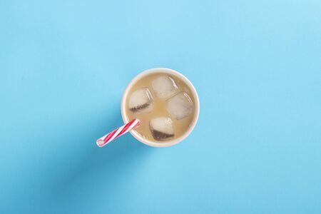 Refreshing coffee with milk and ice in a glass on a blue background. Concept summer, ice, refreshing cocktail, thirst. Flat lay, top view.