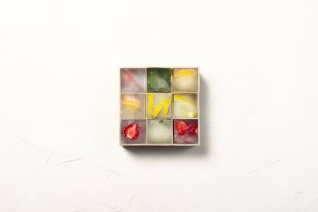 Ice cubes with fruit in silicone mold on a white stone background. Fruit ice concept, quenching thirst, summer. Flat lay, top view.