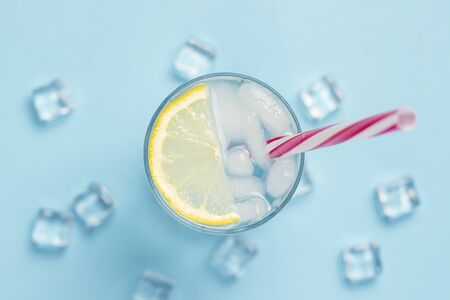 Glass of water or drink with ice and lemon on a blue background with ice cubes. Concept of a hot summer, alcohol, cooling drink, quenching thirst. Flat lay, top view. Stock Photo