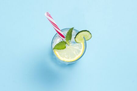 A glass of water or drink with ice, lemon, cucumber and mint on a blue background. The concept of hot summer, alcohol, cooling drink, thirst quenching, bar. Flat lay, top view.