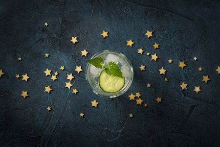 Refreshing Drink with ice, cucumber and mint on a dark blue background with stars. Concept night club, night life, party, thirst. Flat lay, top view.