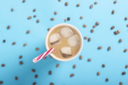 Refreshing coffee with milk and ice in a glass and coffee grains on a blue background. Concept summer, ice, refreshing cocktail, thirst. Flat lay, top view. Stock Photo