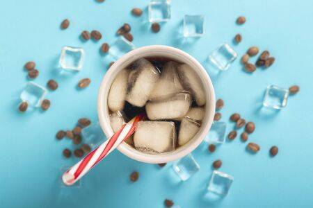 Refreshing iced coffee in a glass and ice cubes and coffee grains on a blue background. Concept summer, cola with ice, refreshing cocktail, thirst. Flat lay, top view. Stock Photo