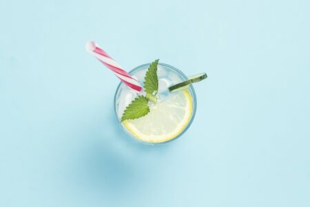 Glass of water or drink with ice, lemon and mint on a blue background. Concept of a hot summer, alcohol, cooling drink, quenching thirst. Flat lay, top view. Stock Photo