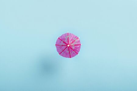 Decorative umbrella for a cocktail on a blue background. Flat lay, top view. Stock Photo