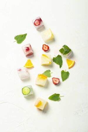 Ice cubes with fruit and mint leaves on a white stone background. Fruit ice concept, quenching thirst, summer. Flat lay, top view. Stock Photo