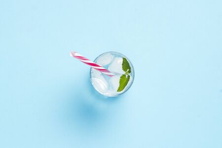 Glass of water with ice and mint on a blue background. Concept of hot summer, alcohol, cooling drink, thirst quenching, bar. Flat lay, top view.