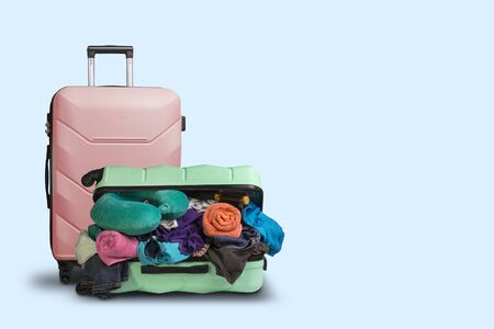Opened plastic suitcase with wheels, crowded with things and a smaller suitcase standing next to a blue background. Travel concept, vacation trip, visit to relatives.