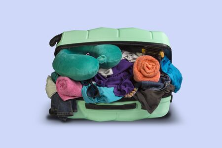 Plastic suitcase with wheels, overflowing things on a blue background. Travel concept, vacation trip, visit to relatives. Фото со стока