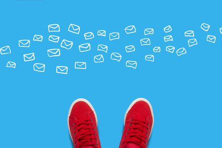 Legs in red sneakers on a blue background with flying white envelopes. Concept of receiving a lot of mails and messages in a trip or way to work. Flat lay, top view.