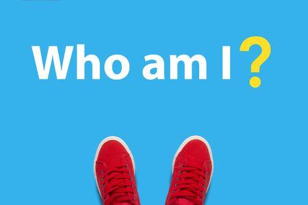 Piernas en zapatillas rojas de pie sobre un fondo azul con el texto ¿Quién soy yo ?. Concepto de autodesarrollo y autoconocimiento. Vista plana endecha, superior. Foto de archivo