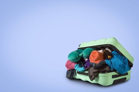 Plastic suitcase with wheels, overflowing things on a blue background. Travel concept, vacation trip, visit to relatives.