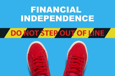Legs in red sneakers on a blue background with a restrictive yellow black stripe with text do not fail and Financial independence behind the line. The concept of dependence on banks, loans, mortgages.