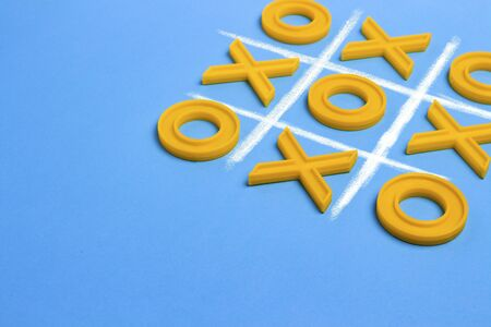 Yellow plastic crosses and a toe and a ruled field for playing tic-tac-toe on a blue background. Concept XO Win Challenge. Educational game for kids.