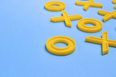 Yellow plastic crosses and zeroches for playing tic-tac-toe on a blue background. Concept XO Win Challenge. Educational game for kids.