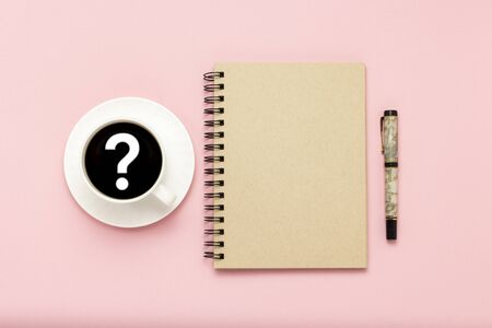 White cup with black coffee, notebook, pen on a pink background. Sign question mark. Flat lay, top view.