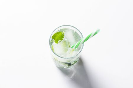 Glass with a cooling drink or water and ice on a light background. Concept of summer cocktails, thirst and heat.