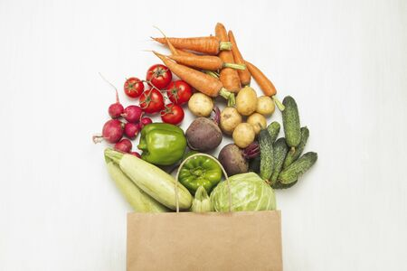 Paper shopping bag and fresh organic vegetables on a white wooden background. Concept of buying farm vegetables, taking care of health, vegetarianism. Country style, Farm Fair. Flat lay, top view. 写真素材