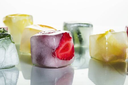 Ice cubes with fruit on a bright white background. The concept of hot summer, dessert, ice cream. Flat lay, top view.