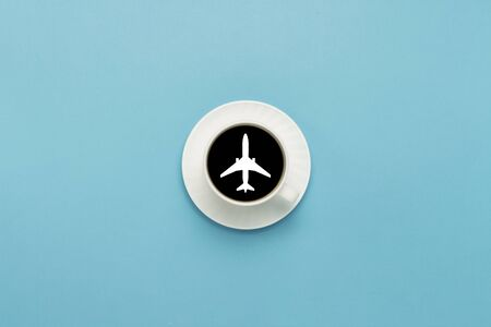 White cup on a saucer, black coffee, blue background. Airplane sign. Flat lay, top view.