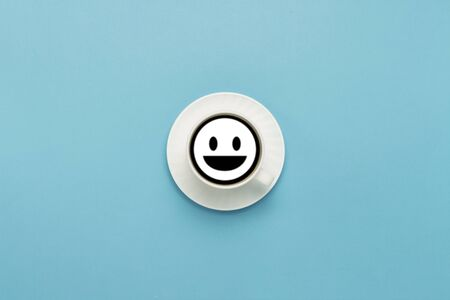 White cup on a saucer, black coffee, blue background. Sign face with a smile. Flat lay, top view.