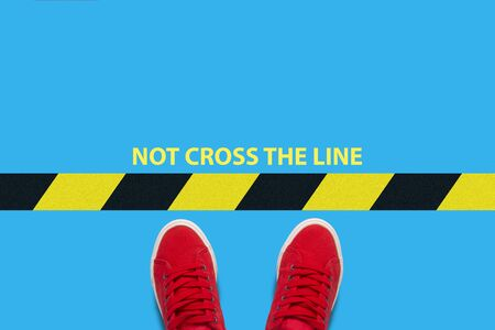 Legs in red sneakers on a blue background a restrictive blak yellow stripe with text not cross the line. Concept of limiting human actions and freedoms. Flat lay, top view.