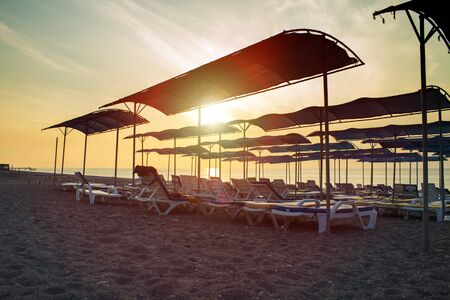 Beach with umbrellas and deck chairs, sun loungers at sunset or sunrise. 写真素材