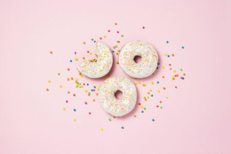Fresh tasty sweet donuts, multicolored decorative candies, sugar cubes on a pink background. Bakery concept, fresh pastries, delicious breakfast, fast food. Flat lay, top view