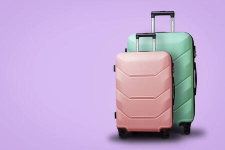 Two Suitcases on wheels on a violet background. Ð¡oncept of travel, a vacation trip, a visit to relatives. Pink and Green color.