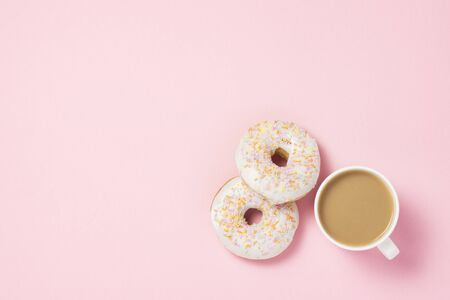 White Cup, coffee or tea with milk and fresh tasty sweet donuts on a pink background. Bakery concept, fresh pastries, delicious breakfast, fast food. Flat lay, top view 写真素材