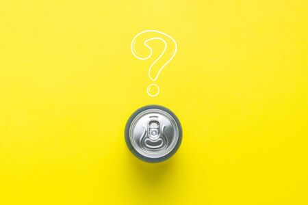 Tin can with a drink on a yellow background with a question mark. minimalism. Concept of an unknown drink, try the first time Flat lay, top view 写真素材