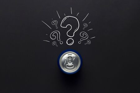 Tin can with a drink on a black background with a question mark. minimalism. Concept of an unknown drink, try the first time Flat lay, top view