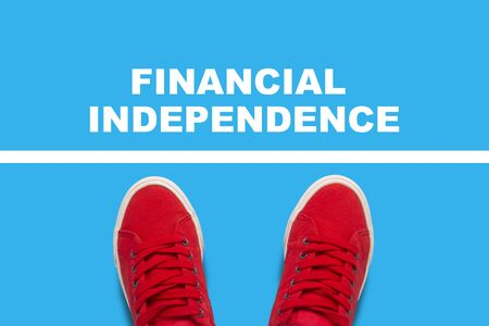 Female legs in red sneakers standing in front of the white line with the text Financial independence behind the line. Concept of financial dependence. Flat lay, top view.