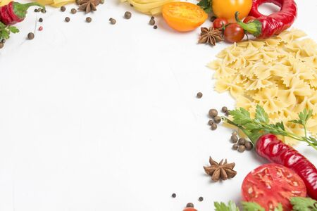 Italian pasta of different kinds with spices, red hot pepper, eggs, yellow and red tomatoes on a white stone background. Concept cooking Italian pasta and sauce. 写真素材