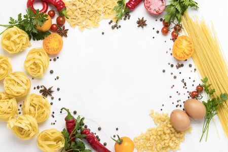 Italian pasta of different kinds with spices, red hot pepper, eggs, yellow and red tomatoes on a white stone background. Concept cooking Italian pasta and sauce. Flat lay, top view. circle shape.