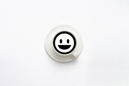White cup on a saucer, black coffee, white background. Sign face with a smile. Flat lay, top view. 写真素材