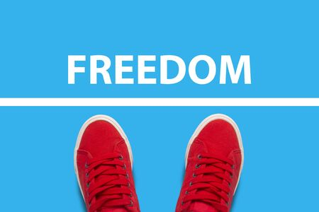 Female legs in red sneakers standing in front of the white line with the text Freedom behind the line. Concept of limiting freedom and action. Flat lay, top view. 写真素材