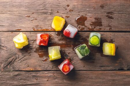 Ice cubes with fruit on wooden background. The concept of hot summer dessert. Flat lay, top view.
